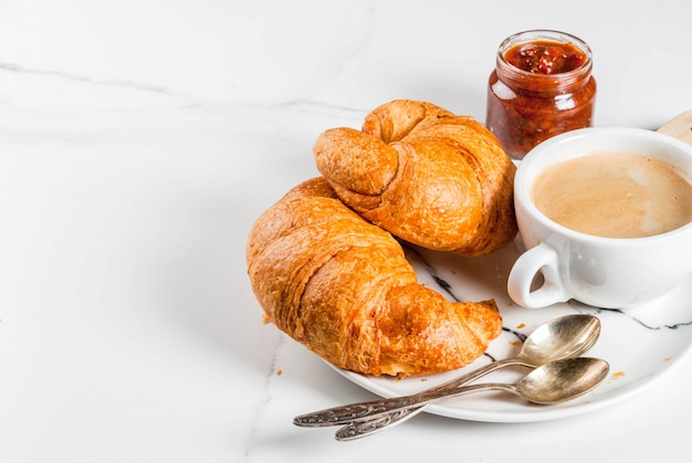 Homemade continental breakfast, coffee croissants. jam on white marble table, copyspace