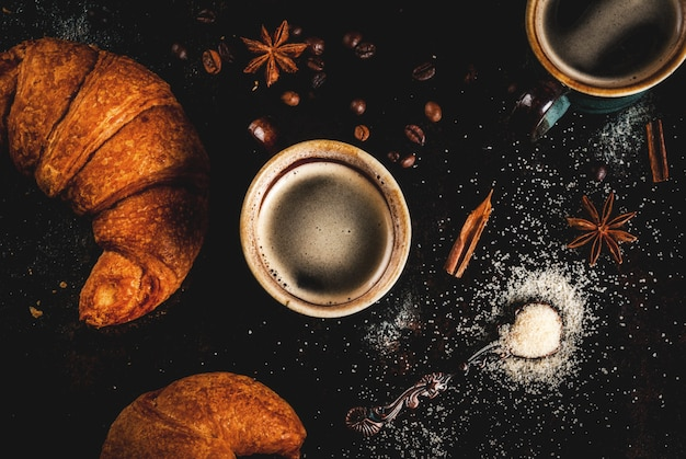 Homemade continental breakfast, coffee with spice, cane sugar, croissants. jam on a black rusty metal table, top view copyspace