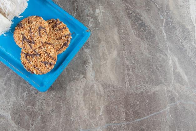Домашнее печенье и турецкая сахарная вата на деревянной тарелке на синем.