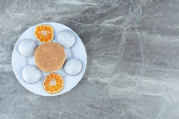 말린 오렌지 조각을 곁들인 홈메이드 쿠키와 와플.
