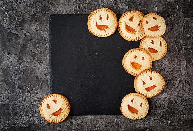Biscotti fatti in casa sotto forma di zucche di halloween jack-o-lantern sul tavolo scuro. vista dall'alto.