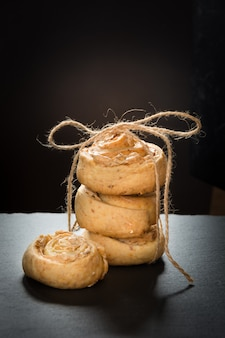 Homemade cookies from cottage cheese and meringue, tied up twine with cup of coffee on black slate dish