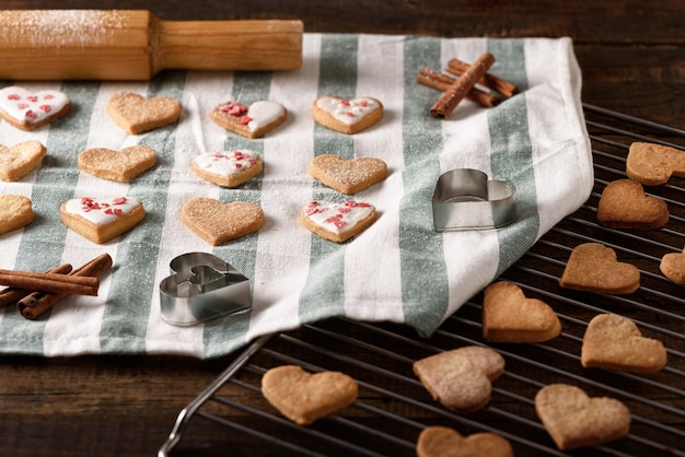 Homemade cookies hearts with white icing and pastry topping on kitchen towel and metal grate, handmade concept