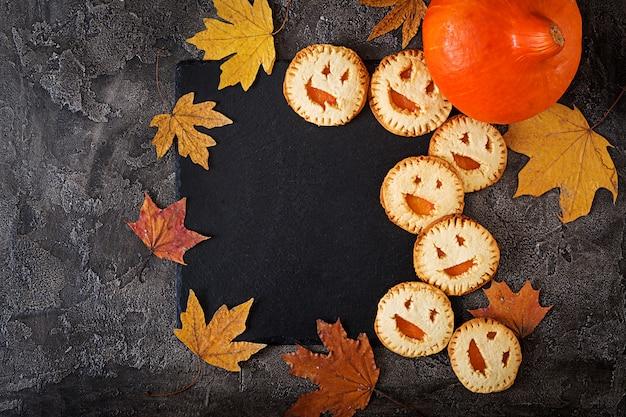 Домашнее печенье в виде хэллоуина тыквы на темном столе. вид сверху.