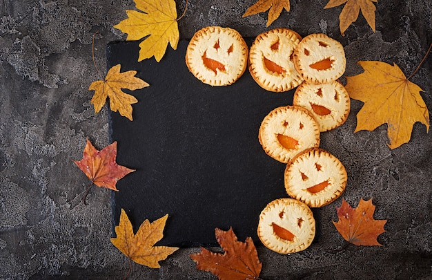 暗いテーブルの上のハロウィンジャック-o-ランタンカボチャの形の自家製クッキー。上面図。