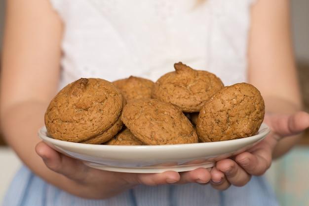 女の子の手にある自家製クッキー、自家製ケーキ