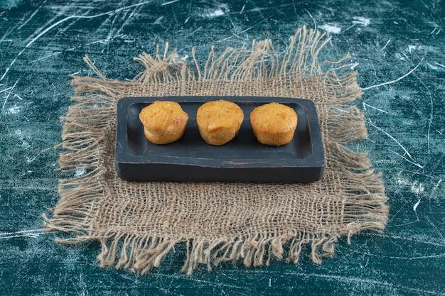 Домашнее печенье на деревянной тарелке на полотенце, на синем фоне. фото высокого качества