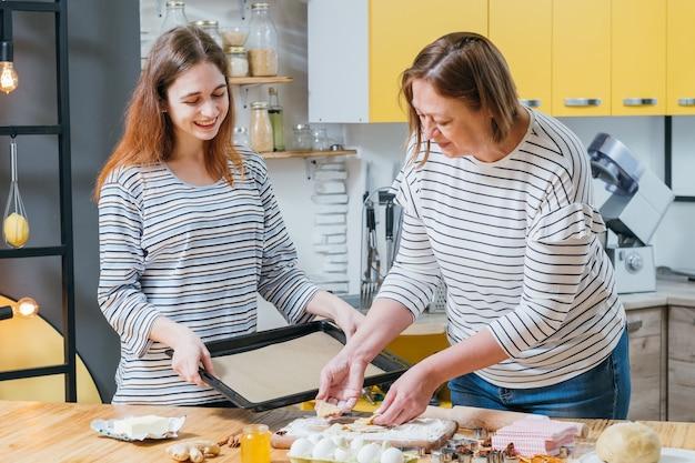 수제 쿠키 레시피. 어머니가 요리를 돕는 딸, 진저 비스킷 용 시트 팬을 들고.