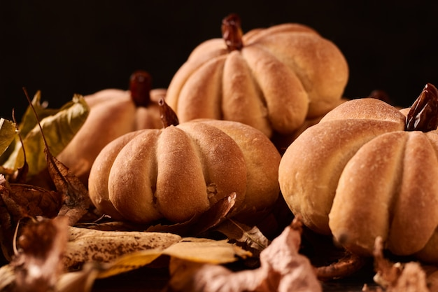 Homemade cookies in shape of pumpkin in autumn leaves. halloween handmade cookies on a table, close up