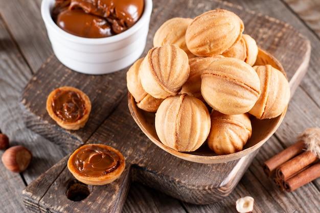 Домашнее печенье в форме орехов с вареной сгущенкой на деревянном столе