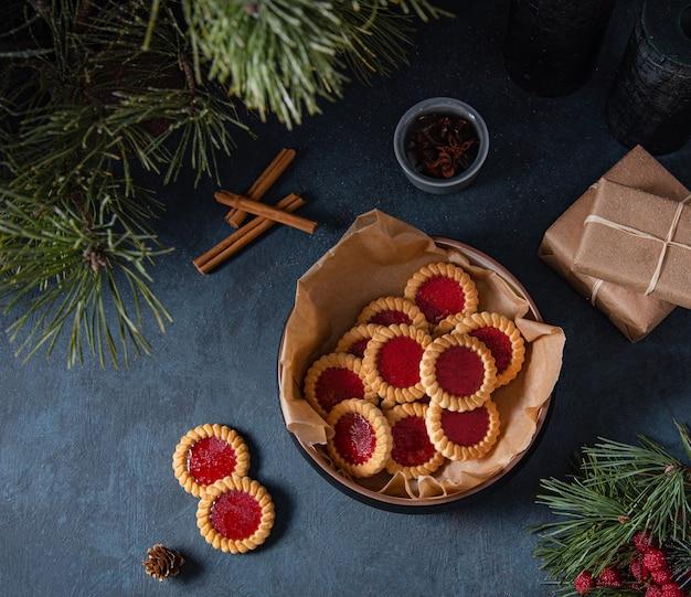 シナモン、プレゼントボックス、モミの木が入った紺色のテーブルのボウルにフルーツジャムが入った自家製クッキー。暗くて気分のイメージ。上面図