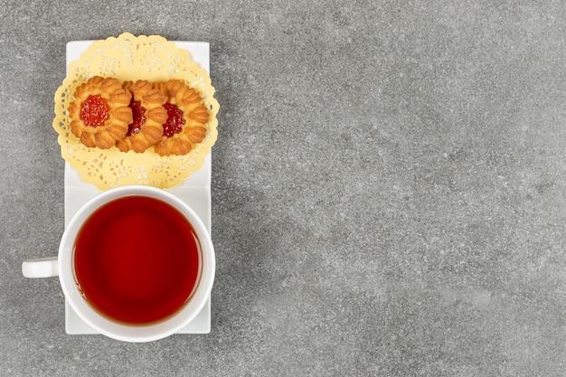 젤리와 하얀 접시에 차 한잔으로 만든 쿠키