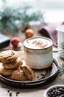 Homemade cookies with nuts and coffee in a ceramic cup on a wooden table with toys and christmas tree branches.