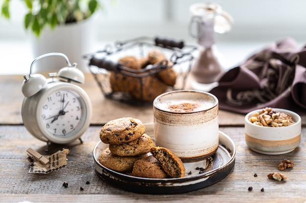 Homemade cookies with nuts and coffee in a ceramic cup on a wooden table.