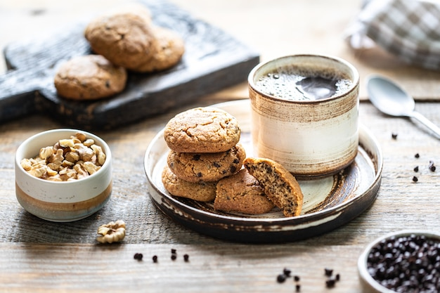 Homemade cookies with nuts and hot coffee in a ceramic cup