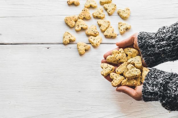 ホワイトボードにハートの形をしたターメリックと亜麻の種子を使った自家製クッキー。クッキーは手元にあります。バレンタインデーの食べ物。上からの眺め。