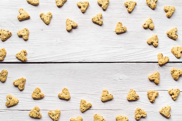 ホワイトボードにハートの形をしたターメリックと亜麻の種子を使った自家製クッキー。バレンタインデーの食べ物。クッキーの楕円形のフレーム。上からの眺め。