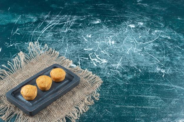 Biscotti fatti in casa su un piatto di legno su un asciugamano, sullo sfondo blu. foto di alta qualità