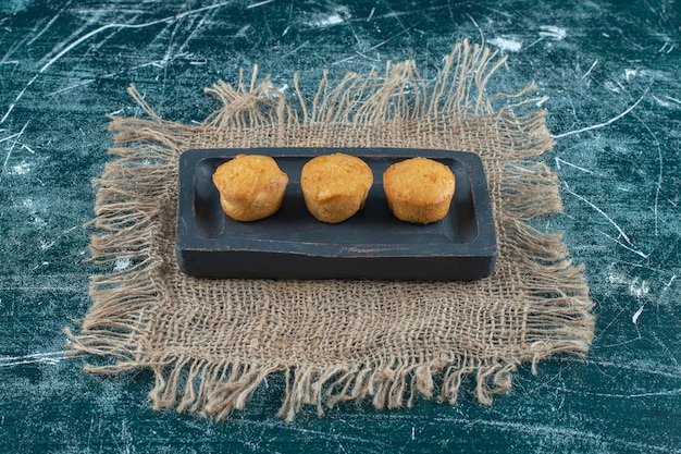 Homemade cookies on a wooden plate on towel , on the blue background. high quality photo