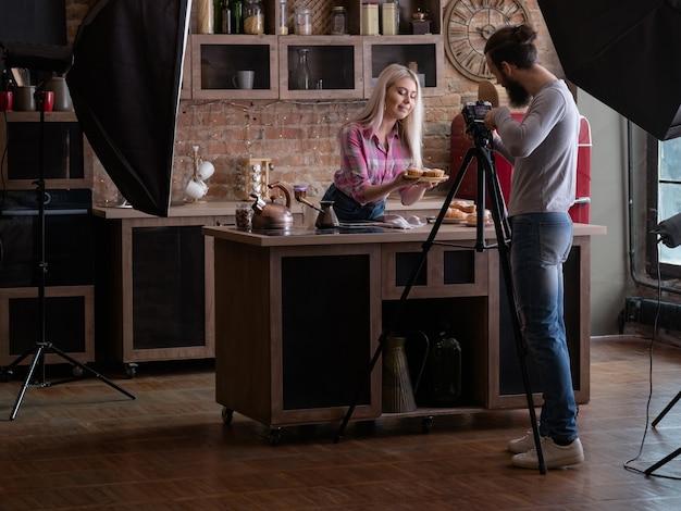 수제 요리. 베이킹 취미. 백 스테이지 사진. 신선한 케이크와 파이를 가진 남자 촬영 여자.