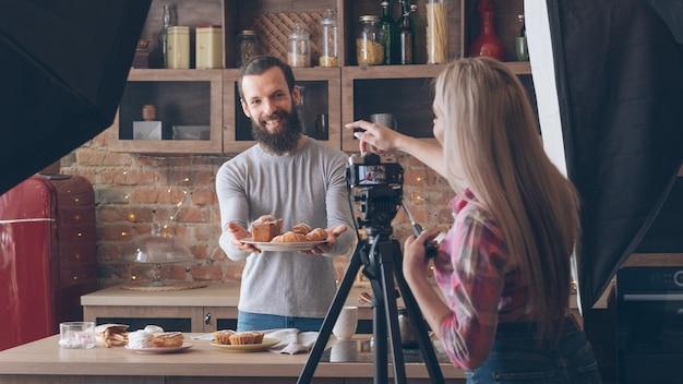 수제 요리. 베이킹 취미. 백 스테이지 사진. 신선한 케이크와 파이 웃는 남자를 촬영하는 여자.