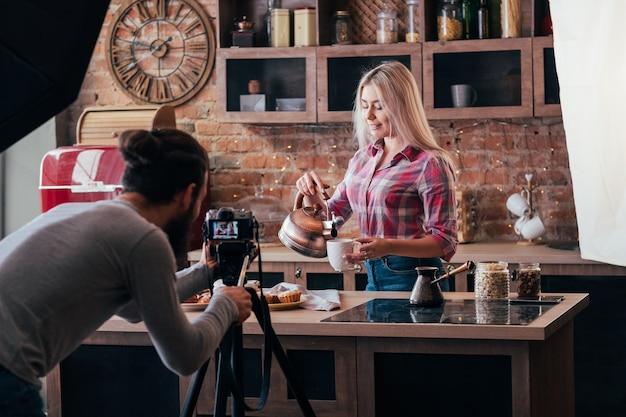 수제 요리. 베이킹 취미. 백 스테이지 사진. 구리 주전자와 파이를 가진 여자입니다. 카메라를 가진 남자.