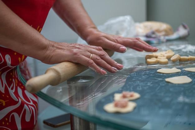 キッチンで女性の手で餃子を手作り。