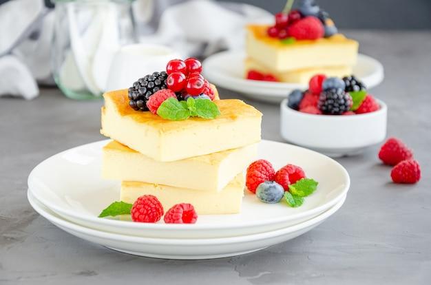 白いプレートの上に新鮮なベリーとミントを乗せた自家製カッテージチーズのキャセロール。健康的な朝食。水平方向のコピースペース。