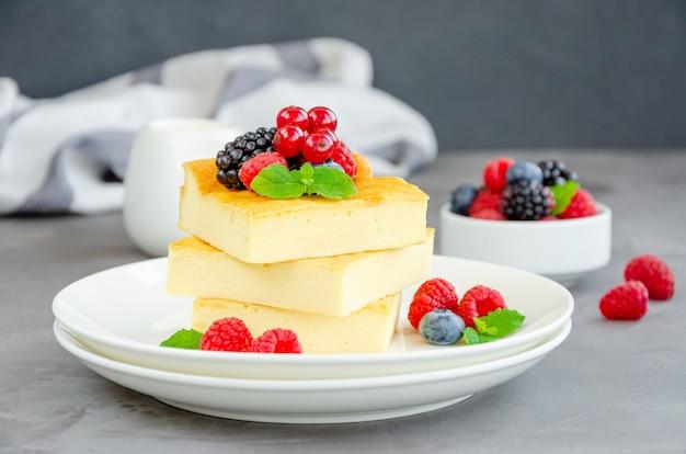 Домашняя творожная запеканка со свежими ягодами и мятой сверху на белой тарелке. здоровый завтрак. горизонтально, скопируйте пространство.