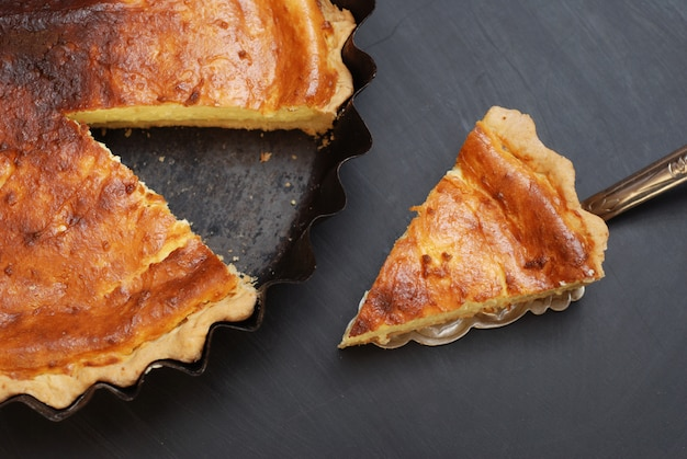 Homemade cottage cheese pie or cake, slices on black slate.