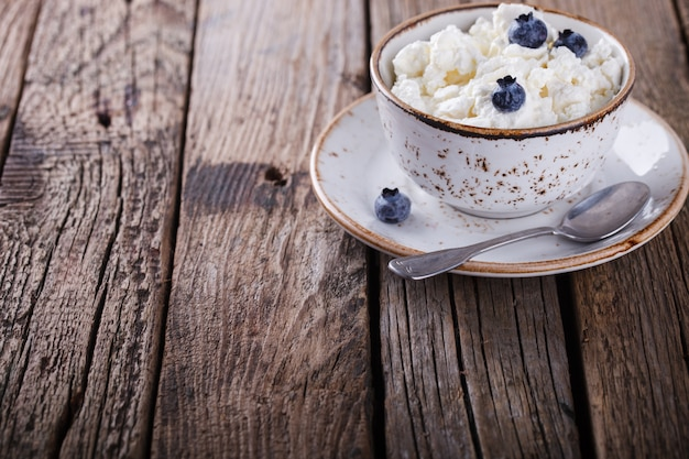 Homemade cottage cheese in a plate, with blueberries.