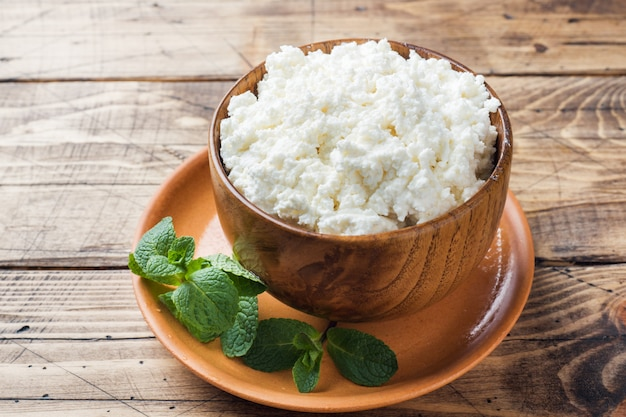 Homemade cottage cheese with mint in a bowl on old wooden table. copy space