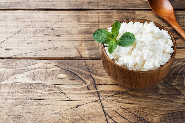 Homemade cottage cheese with mint in a bowl on old wooden table.