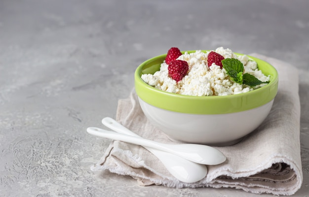 Homemade cottage cheese with raspberry and mint in a bowl