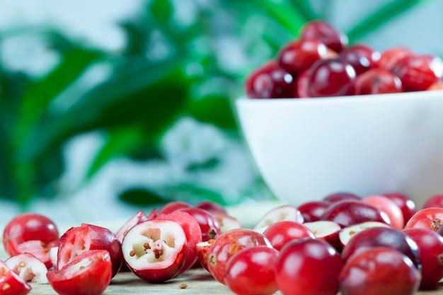 Домашняя клюква, выращенная в промышленном саду, нарезанная дольками, красная нарезанная кислая полезная клюква, красная спелая клюква на столе