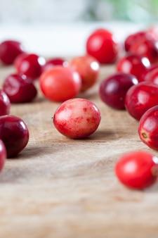 工業用庭園で栽培された自家製クランベリー、赤い酸っぱい健康的なクランベリー、テーブルの上の赤い熟したクランベリー
