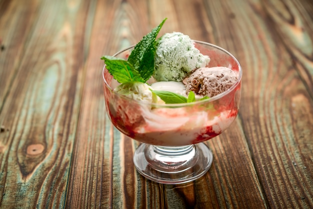 Homemade cranberry ice cream and mint sprig in a wooden bowl