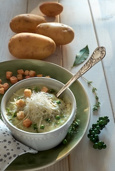 Homemade cream of potato soup in mug with croutons, parmesan cheese and thyme