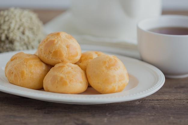 自家製クリームパフまたはチョコクリームまたはeclairsは、白い鍋またはcoffeのカップでお茶を提供しています