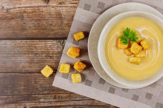 テーブルの上のクルトンと自家製のクリーミーなエンドウ豆のスープ