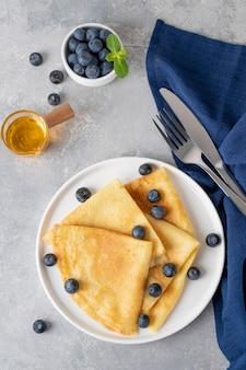 수제 크레페는 회색 콘크리트 배경에 흰색 접시에 신선한 블루 베리와 가루 설탕을 곁들였습니다. maslenitsa를위한 음식. 공간을 복사하십시오.