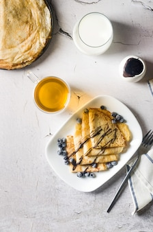 自家製クレープ、白いプレートにチョコレートとベリーを添えたおいしい薄いパンケーキをお茶と一緒に朝食に。伝統的なロシア料理。