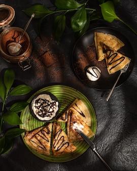 어두운 테이블에 초콜릿과 아이스크림으로 만든 크레페. 가정 요리