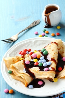 Homemade crepes with multicolored dragee and chocolate sauce on blue wooden background