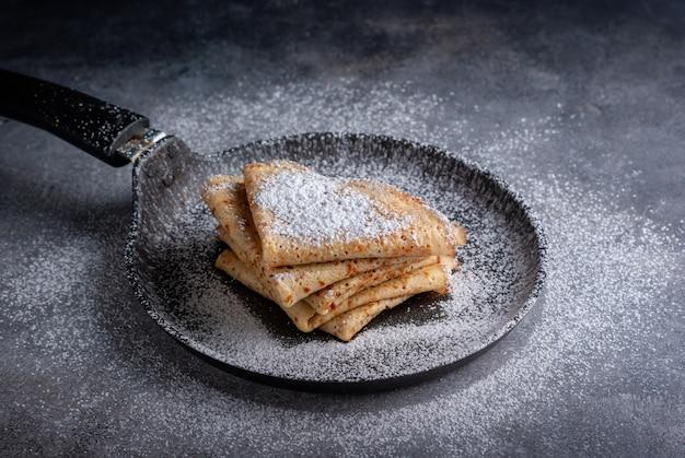 Домашние блины с сахарной пудрой на темном столе в железной сковороде