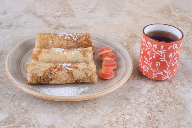 Crepes fatte in casa con zucchero in polvere e una tazza di tè