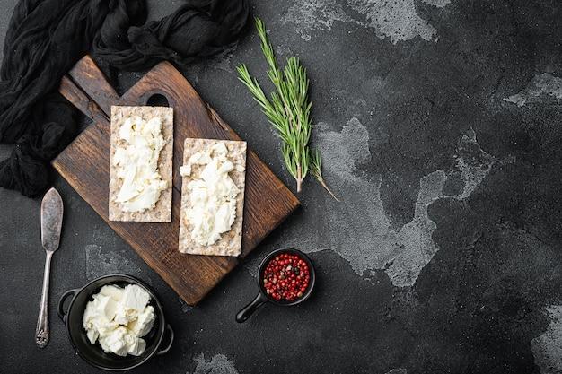 검은 어두운 돌 테이블에 코티지 치즈 세트로 만든 바삭 바삭한 빵 토스트, 평면도 평면 누워