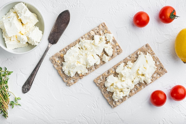 흰색 돌 테이블 배경에 코티지 치즈 세트가 있는 홈메이드 크리스프 빵 토스트, 텍스트 복사 공간이 있는 평면도