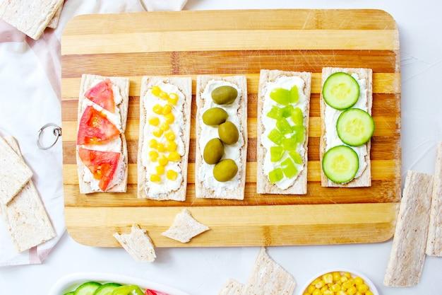 Домашние хрустящие хлебцы с творогом и зелеными оливками, кусочками капусты, помидорами, кукурузой, зеленым перцем на разделочной доске. концепция здорового питания, вид сверху. плоская планировка