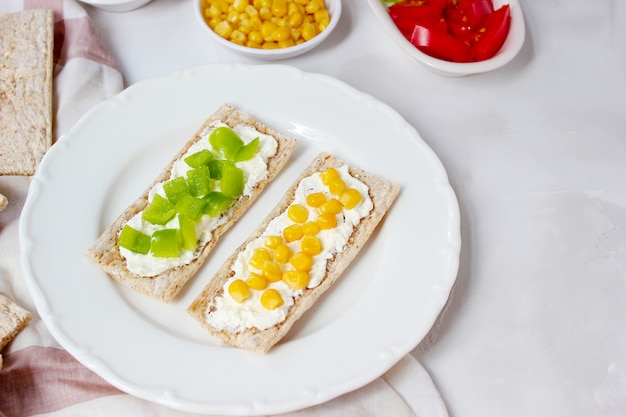 Homemade crispbread toast with cottage cheese and green olives, slices of cabbage, tomatoes, corn, green pepper on cutting board. healthy food concept, top view. flat lay